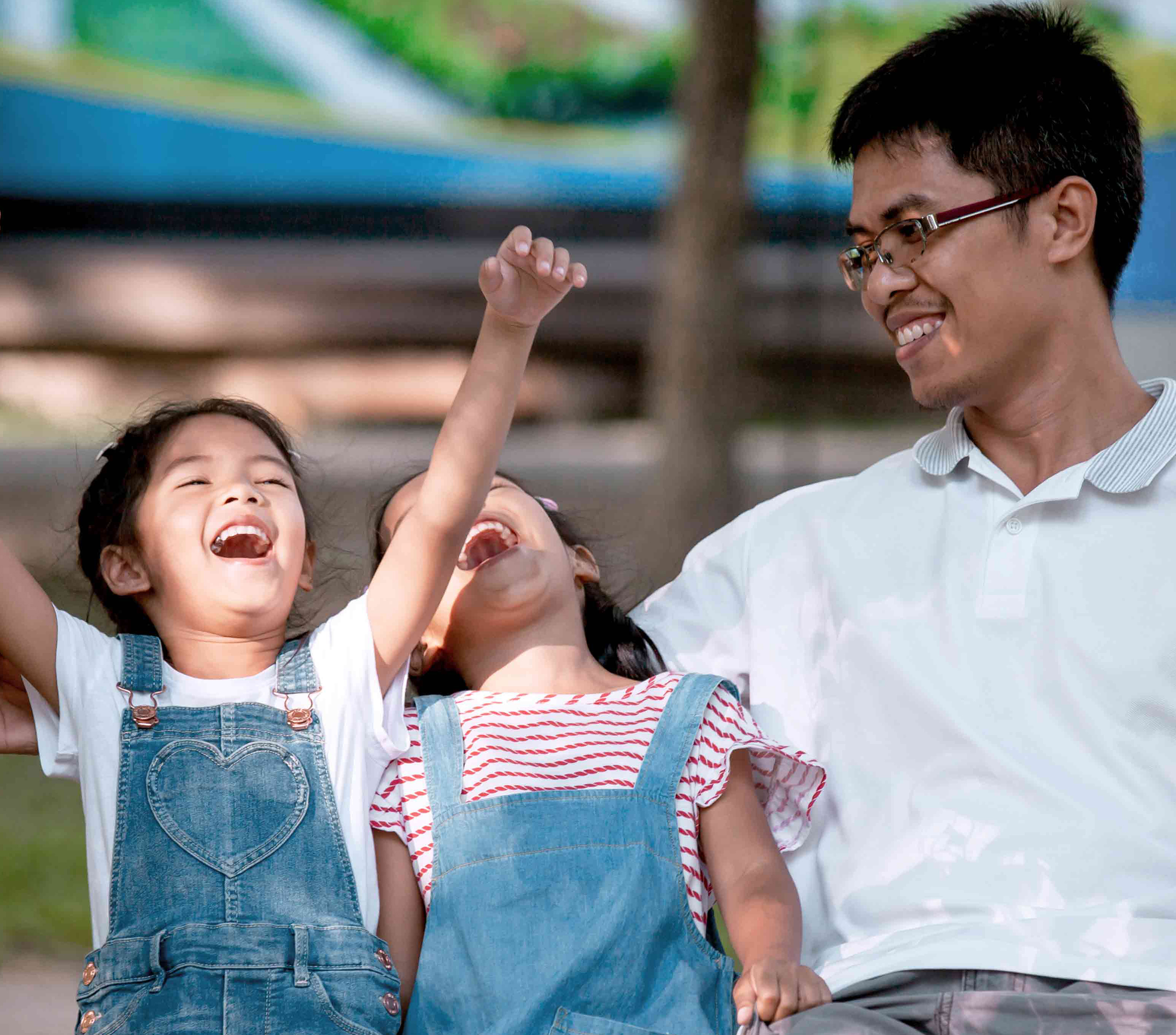 Man and his two daughters laughing and cheering on a bench