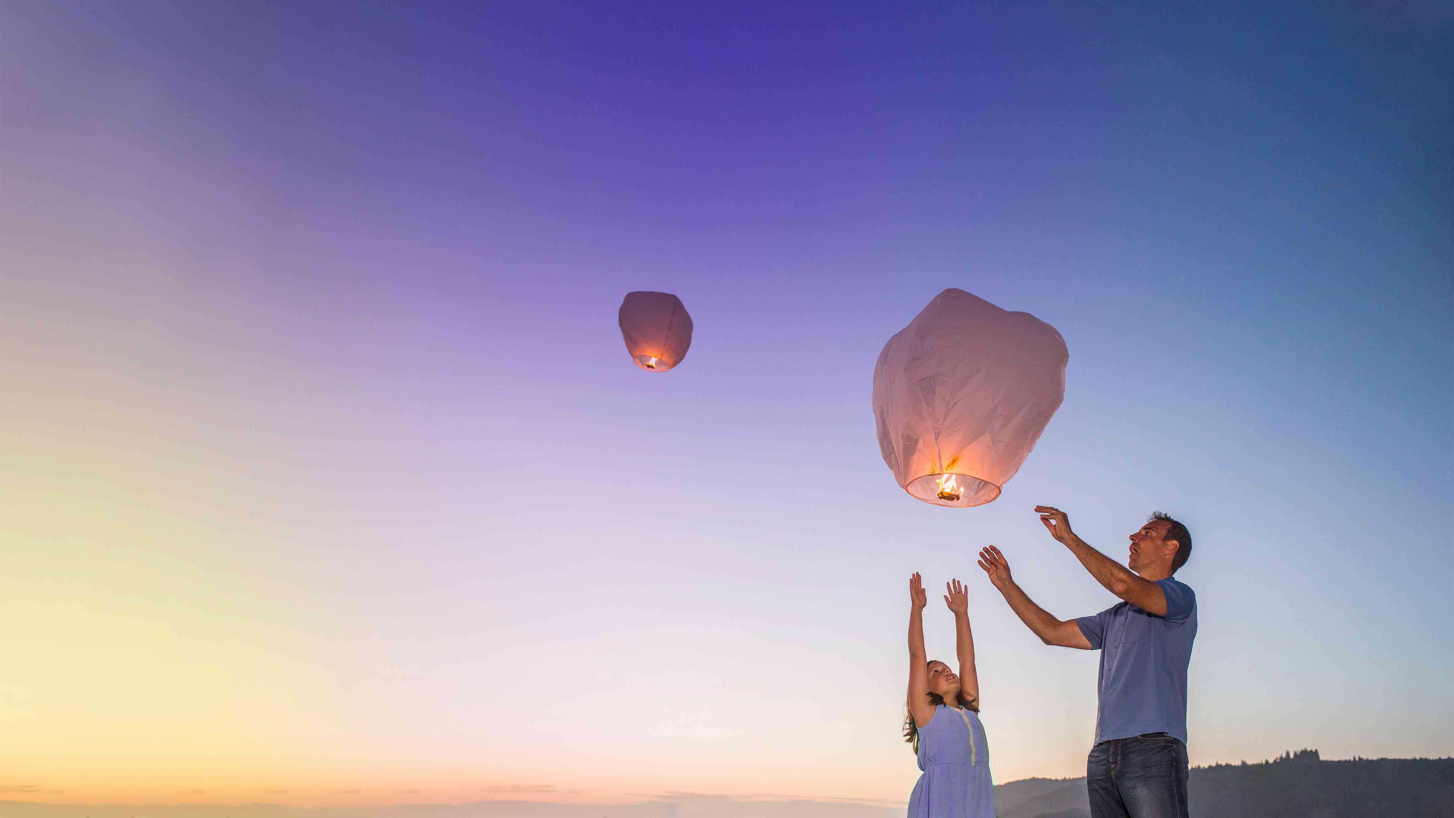 Father and daughter release white paper lanterns into the sky